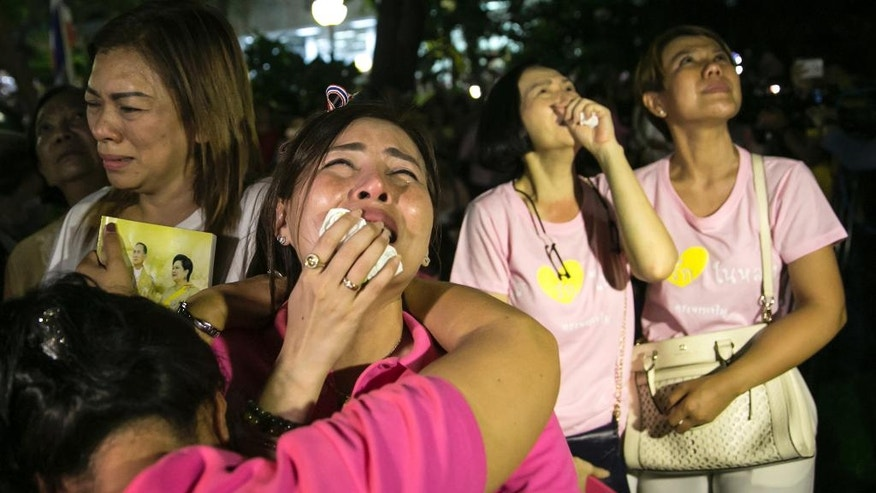 People react, at Siriraj Hospital where the king is being treated in Bangkok, Thailand, Thursday, Oct. 13, 2016. Thailand's Royal Palace says King Bhumibol, the world's longest-reigning monarch, has died at age 88. (AP Photo/Wason Wanichakorn)