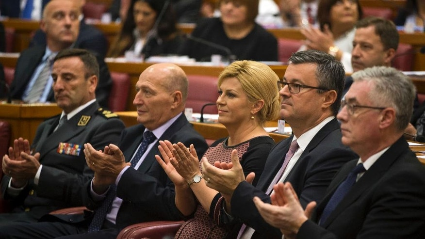 Croatian president Kolinda Grabar-Kitarovic, center and outgoing prime minister Tihomir Oreskovic, center right, applaud as Croatian Parliament convenes in Zagreb, Croatia, Friday, Oct. 14, 2016. The ninth 151-member Croatian Parliament was inaugurated following the Sept. 11, 2016 snap election. (AP Photo/Darko Bandic)