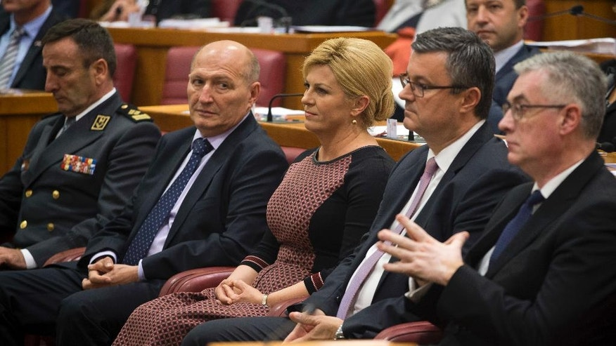 Croatian president Kolinda Grabar-Kitarovic, center and outgoing prime minister Tihomir Oreskovic, center right, attend a Parliament session in Zagreb, Croatia, Friday, Oct. 14, 2016. The ninth 151-member Croatian Parliament was inaugurated following the Sept. 11, 2016 snap election. (AP Photo/Darko Bandic)