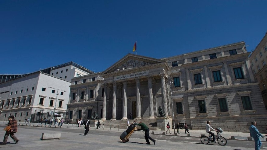 FILE - In this Tuesday, May 3, 2016 file photo, a worker pushes a trolley past the Spanish Parliament in Madrid, Spain, Tuesday, May 3, 2016. Spain is about to pass 300 days without a government. But guess what? Few people seem very bothered by that as the economy roars ahead. In Spanish cities there are packed terrace cafes and restaurants, thriving fashion shops and art galleries. The overall impression is of a bustling and vibrant country pressing forward. (AP Photo/Paul White, File)