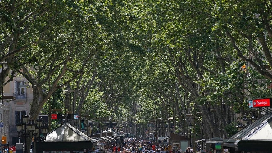 FILE - In this Wednesday, May 25, 2016 file photo, tourists walk along the Ramblas street in Barcelona, Spain. Spain is about to pass 300 days without a government. But guess what? Few people seem very bothered by that as the economy roars ahead. In Spanish cities there are packed terrace cafes and restaurants, thriving fashion shops and art galleries. The overall impression is of a bustling and vibrant country pressing forward. (AP Photo/Manu Fernandez, File)