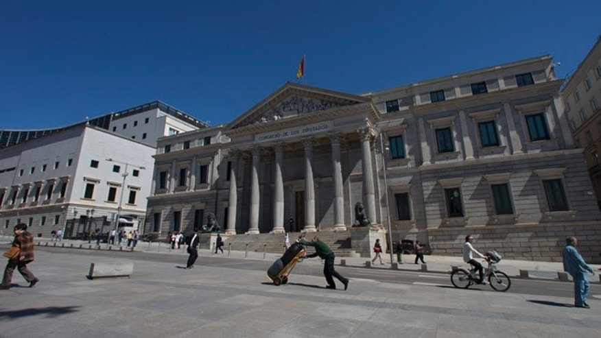 In this Tuesday, May 3, 2016 file photo, a worker pushes a trolley past the Spanish Parliament in Madrid, Spain, Tuesday, May 3, 2016. Spain is about to pass 300 days without a government. But guess what? Few people seem very bothered by that as the economy roars ahead. In Spanish cities there are packed terrace cafes and restaurants, thriving fashion shops and art galleries. The overall impression is of a bustling and vibrant country pressing forward. (AP Photo/Paul White, File)