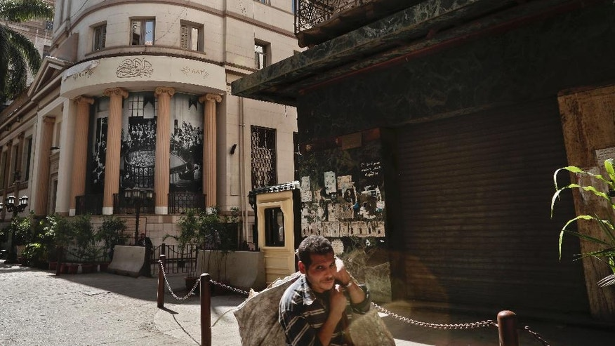 A garbageman walks past the stock market in downtown Cairo, Egypt, Thursday, Oct. 13, 2016. Egypt is inching toward meeting conditions for a bailout package from the International Monetary Fund, as hard currency and some products become increasingly scarce while an escalating spat with key backer Saudi Arabia overshadows. (AP Photo/Nariman El-Mofty)