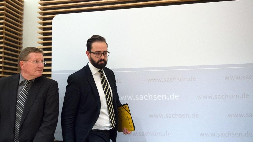 Rolf Jacob, director of the prison in Leipzig, left, and Saxony's state justice minister Sebastian Gemkow srrive for a press conference in Dresden, eastern Germany, Thursday, Oct. 13, 2016 after the death of 22-year-old Syrian man Jaber Albakr suspected of planning an Islamic extremist bombing attack strangled himself by tying his shirt to the bars of his jail cell. (Arno Burgi/dpa via AP)