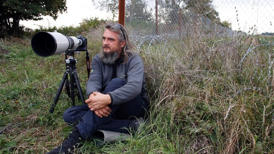 In this photo from Sunday, Oct. 9, 2016, Croatian photographer and environmentalist Mario Romulic who has spent months documenting the plight of animals in Baranya and rising alarms on social networks, sits next to the border fence near Knezevo, northeast Croatia, on the border with Hungary. Thousands of deer and other wild animals have become the unintended victims of Hungary's attempts to prevent migrants crossing the border from Croatia _ their natural habitat is disrupted by kilometers of barbed wire fence. (AP Photo/Darko Bandic)