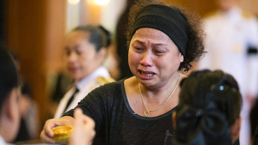 A mourner pours holy water into a bowl as part of a bathing ceremony for Thai King Bhumibol Adulyadej at Grand Palace in Bangkok, Thailand, Friday, Oct. 14, 2016. Thailand began its first day in 70 years without a king on Friday in a profound state of mourning, with people across the shaken nation dressed in black following the death of the world's longest-reigning monarch. (AP Photo/Wason Wanichakorn)