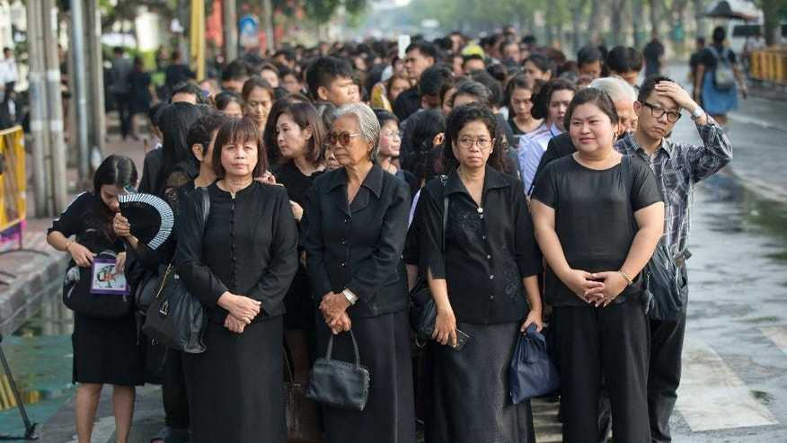 Thai people stand in lines to offer condolences for Thai King Bhumibol Adulyadej at Grand Palace in Bangkok, Thailand, Friday, Oct. 14, 2016. Grieving Thais went to work dressed mostly in black Friday morning, just hours after the palace announced the death of their beloved King Bhumibol, the politically fractious country's unifying figure and the world's longest-reigning monarch.(AP Photo/ Gemunu Amarasinghe)