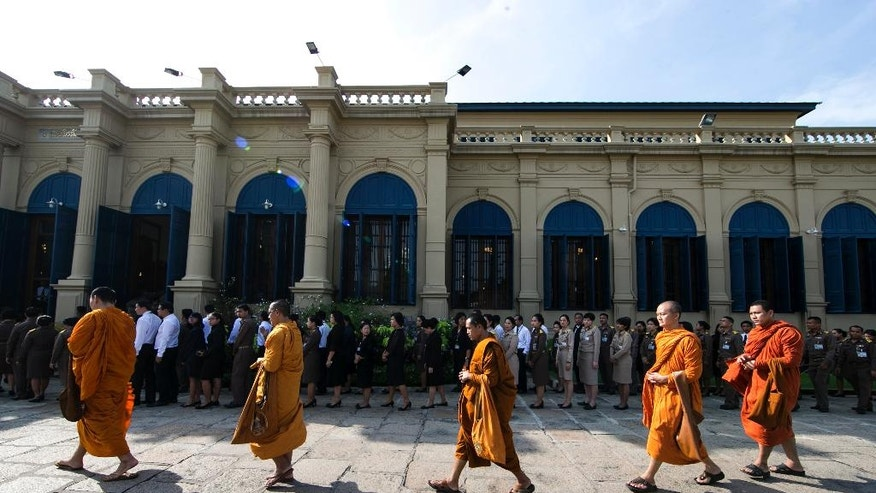 Buddhist monks and Thais line up to offer condolences for Thailand's King Bhumibol Adulyadej at Grand Palace in Bangkok, Thailand, Friday, Oct. 14, 2016. Thailand began its first day in 70 years without a king on Friday in a profound state of mourning, with people across the shaken nation dressed in black following the death of the world's longest-reigning monarch. (AP Photo/Wason Wanichakorn)