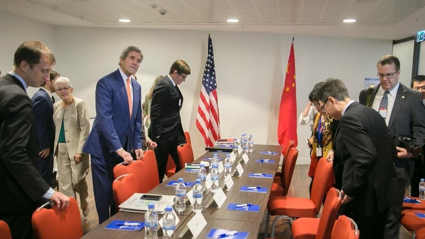 U.S. Secretary of State John Kerry, center-left, prepares for a bilateral meeting with the Chinese delegation, on the sidelines of the 28th Meeting of the Parties to the Montreal Protocol on Substances that Deplete the Ozone Layer, in Kigali, Rwanda, Friday, Oct. 14, 2016.  Nations strove Friday for a deal to phase out hydrofluorocarbons from air conditioners and refrigerators as part of efforts to fight climate change. (AP Photo)