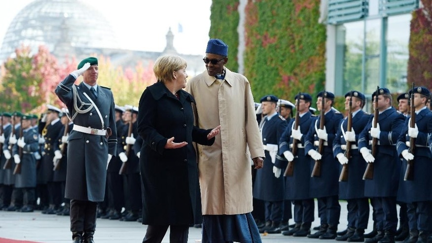 German Chancellor Angela Merkel,  left, and  the President of Nigeria Muhammadu Buhari, right, review the honor guards prior to  talks at the chancellery in Berlin, Friday, Oct. 14, 2016..  (Rainer Jensen, dpa via AP)