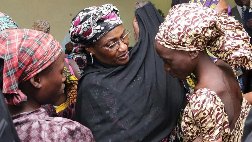 In this photo released by the Nigeria State House, an unidentified government official, center, welcomes some of the freed Chibok school girls at the state House in Abuja, Nigeria, Thursday, Oct. 13, 2016. Twenty-one of the Chibok schoolgirls kidnapped by Boko Haram more than two years ago were freed Thursday in a swap for detained leaders of the Islamic extremist group — the first release since nearly 300 girls were taken captive in a case that provoked international outrage. (Sunday Aghaeze/Nigeria State House via AP)