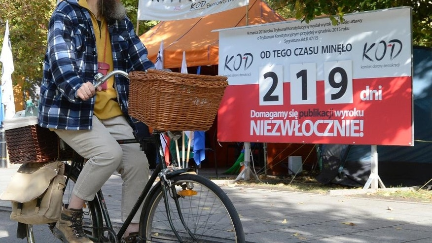 "A cyclist rides past a board indicating the number of days that have passed since a key Constitutional Tribunal ruling against legal changes to the way the court functions, in front of the government office, in Warsaw, Poland, Friday, Oct. 14, 2016. An international human rights body, the Venice Commission, has criticized Friday the new legislation in Poland regulating the Constitutional Tribunal, the nation's top legislative court, saying the new law ""gives excessive power to parliament and the executive over the judiciary."" (AP Photo/Alik Keplicz)"