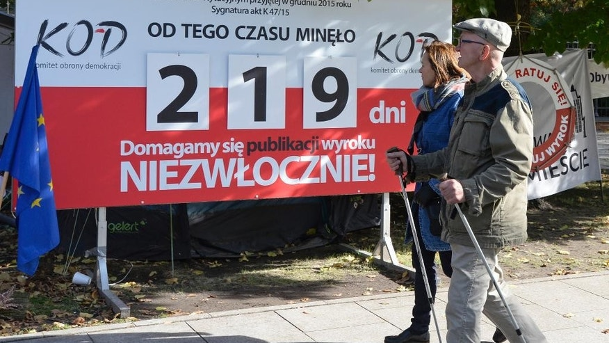 "People walk past a board indicating the number of days that have passed since a key Constitutional Tribunal ruling against legal changes to the way the court functions, in front of the government office in Warsaw, Poland, Friday, Oct. 14, 2016. An international human rights body, the Venice Commission, has criticized Friday the new legislation in Poland regulating the Constitutional Tribunal, the nation's top legislative court, saying the new law ""gives excessive power to parliament and the executive over the judiciary."" (AP Photo/Alik Keplicz)"
