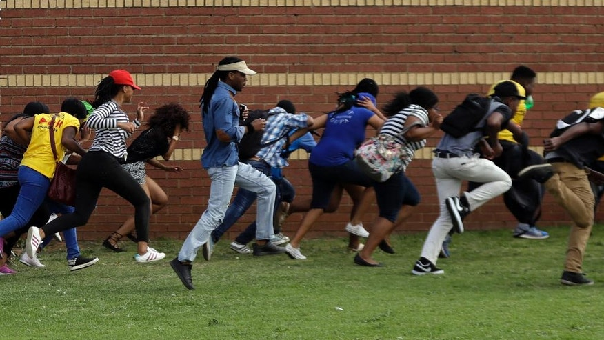 Protesting students run for cover as riot police officers fire rubber bullets at the Vaal University of Technology in Vanderbijlpark, South Africa, on Friday, Oct. 14, 2016. The campus has been the scene of clashes between police and students demonstrating for free university education. (AP Photo/Themba Hadebe)