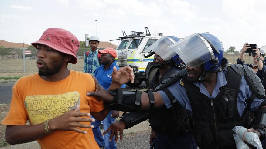 A protesting student is pushed away by riot police officers at the Vaal University of Technology in Vanderbijlpark, South Africa, on Friday, Oct. 14, 2016.  The campus has been the scene of clashes between police and students demonstrating for free university education. (AP Photo/Themba Hadebe)