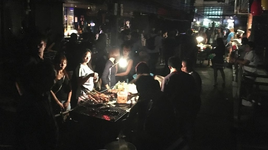 In this Oct. 14, 2016 photo,  people order food from a vendor on a darkened street in Bangkok's Soi Cowboy red-light district, after police and soldiers asked bars owners to shut down following the death Thursday of Thailand's 88-year-old King Bhumibol Adulyadej, who was the world's longest reigning monarch.  Concerts and colossal beach parties in Thailand have been canceled and many seedy go-go bars are closed as the death of revered King Bhumibol Adulyadej plunges this Southeast Asian nation into an unprecedented period of mourning. (AP Photo/Todd Pitman)