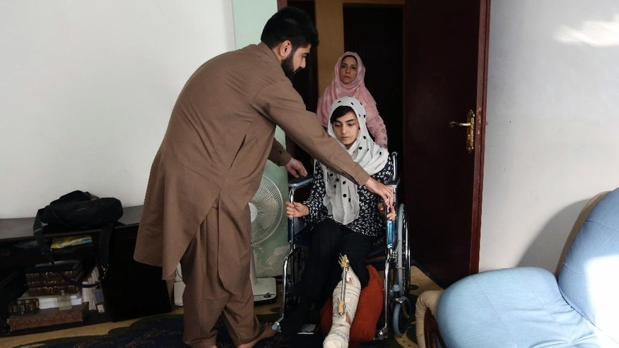 In this Friday, Oct. 7, 2016, photo, Breshna Mosazai, 26, a law student of the American University of Afghanistan, where she was wounded in a Taliban attack, arrives for an interview with the Associated Press at her home in Kabul, Afghanistan. For what felt like an eternity, Mosazai lay in a corridor of the university, playing dead while heavily armed gunmen stalked around her, looking for people to kill. (AP Photo/Rahmat Gul)