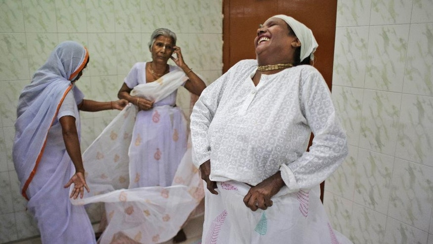 An Indian Hindu widow laughs as she wears a Sari backstage before participating in a fashion show fashion show in New Delhi, India, Saturday, Oct. 15, 2016. Until recently, Indian widows were expected to follow the sociocultural codes of a patriarchal Hindu society that demands a woman lead a life of asceticism after a husband's death. Their lives appear to be changing for better with women's groups and Indian aid organizations taking interest in their welfare. (AP Photo/Altaf Qadri)
