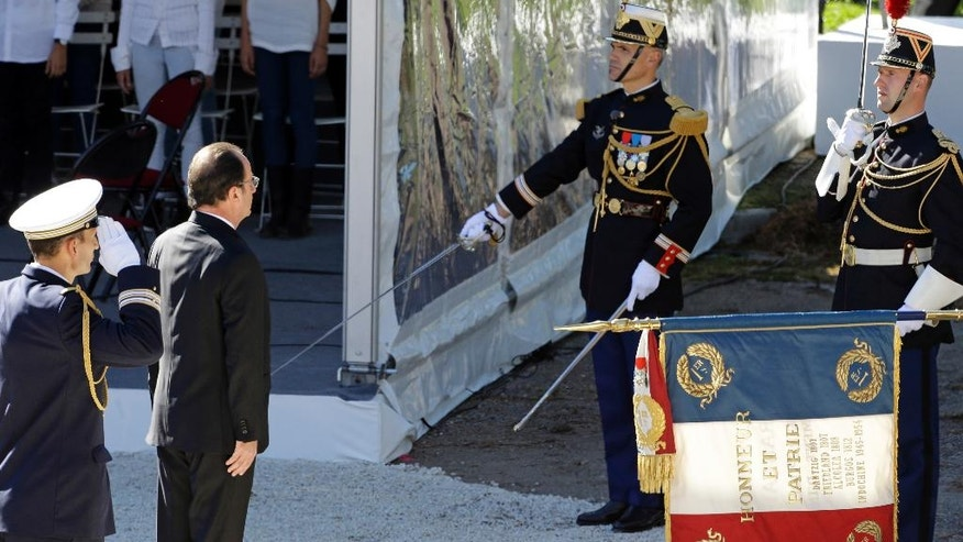 French President Francois Hollande pays respect to the French National flag during ceremony for the victims of July 14 attack in Nice, Saturday, Oct. 15, 2016. French President Francois Hollande attends a ceremony paying homage to the 86 people killed when an Islamic extremist rammed his truck through crowds watching holiday fireworks in Nice. (AP Photo/Claude Paris)