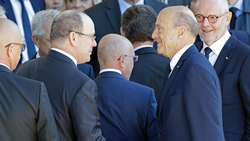 Prince Albert II of Monaco, left, shakes hands with candidate for France's conservative presidential primary Alain Juppe during a ceremony for victims of July 14 attack in Nice, Saturday, Oct. 15, 2016. French President Francois Hollande attends a ceremony paying homage to the 86 people killed when an Islamic extremist rammed his truck through crowds watching holiday fireworks in Nice. (AP Photo/Claude Paris)