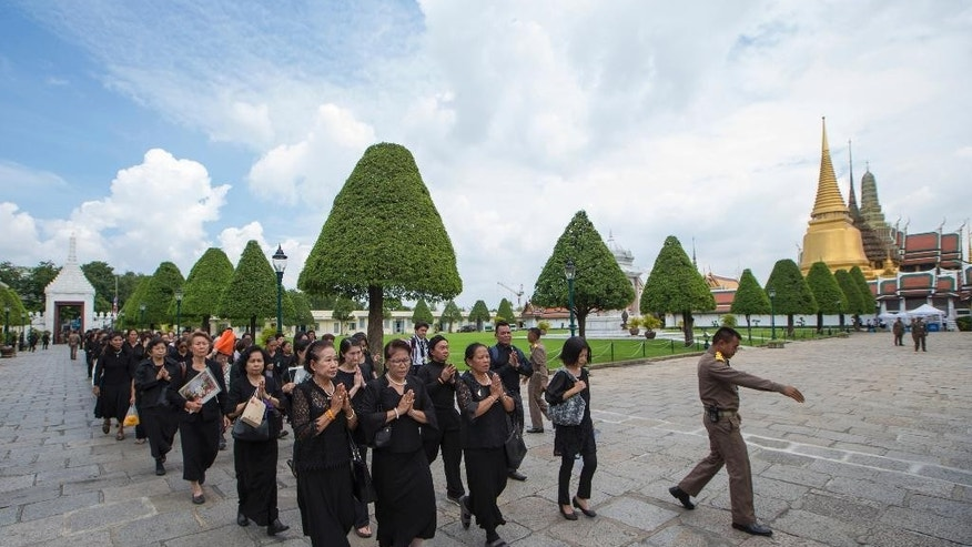 A Thai official, right, guides way for mourners who arrive to pay their respect to the late King Bhumibol Adulyadej at the Grand Palace in Bangkok, Thailand Saturday, Oct. 15, 2016. Thais in their thousands, dressed in somber black and white, descended on the Grand Palace in Bangkok on Saturday to mourn the death of King Bhumibol, who died on Oct. 13, 2016, but were met with the unexpected closure of the complex. (AP Photo/Wason Wanichakorn)