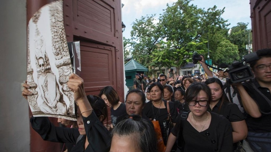 Thai mourners enter the gate to pay their respect to the late King Bhumibol Adulyadej at the Grand Palace in Bangkok, Thailand Saturday, Oct. 15, 2016.  Thailand's government said that a regent will be the caretaker of the monarchy while the country mourns the death of King Bhumibol. Thais in their thousands, dressed in somber black and white, descended on the Grand Palace in Bangkok on Saturday to mourn the death of King Bhumibol, who died on Oct. 13, 2016, but were met with the unexpected closure of the complex. (AP Photo/Wason Wanichakorn)
