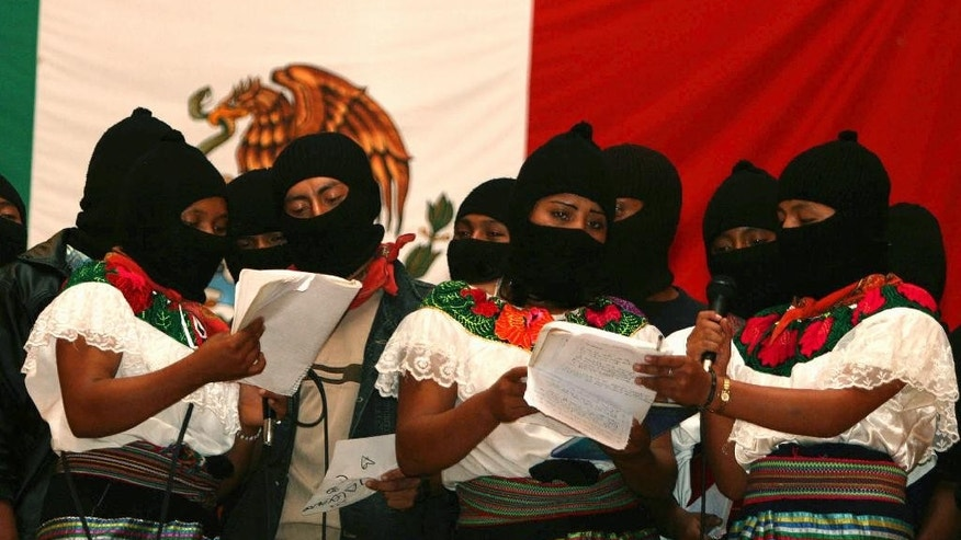 FILE - In this July 24, 2007 file photo, masked female members of the Zapatista National Liberation Army (EZLN), sing during a meeting with supporters in Morelia, Chiapas state, Mexico, after the rebels pledged to move away from armed struggle and toward politics more than a decade after a short-lived revolt for Indian rights and socialism. The EZLN announced on Friday, Oct. 14, 2016 its decision to nominate an indigenous woman as their independent candidate for Mexico's presidency, ahead of 2018 elections. (AP Photo/Moyses Zuniga, File)