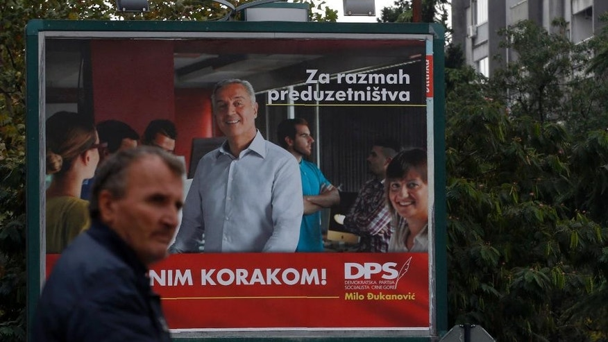 "A man walks by an election poster of pro-Western Prime Minister Milo Djukanovic, leader of the Democratic Party of Socialists, reading: ""With firm step ahead!"", in Podgorica, Montenegro, Saturday, Oct. 15, 2016. Montenegro's general election this weekend will decide whether the small Balkan state continues on a Western course, or becomes ""a Russian colony,"" the country's prime minister said, as he faced the toughest challenge so far to his 25-year rule. (AP Photo/Darko Vojinovic)"