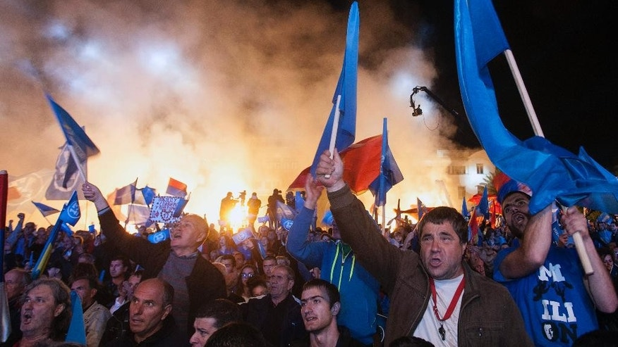 Opposition Democratic Front supporters light torches during a pre-election rally in Podgorica, Montenegro, Friday, Oct. 14, 2016. The Sunday general election in the tiny Balkan nation is the most significant since the vote for independence from much larger Serbia a decade ago. (AP Photo/Risto Bozovic)