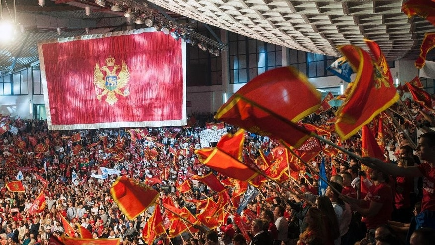 Montenegro's long-ruling Democratic Party of Socialists supporters wave with Montenegro's national flags during a pre-election rally in Podgorica, Montenegro, Friday, Oct. 14, 2016. The Sunday general election in the tiny Balkan nation is the most significant since the vote for independence from much larger Serbia a decade ago. (AP Photo/Risto Bozovic)