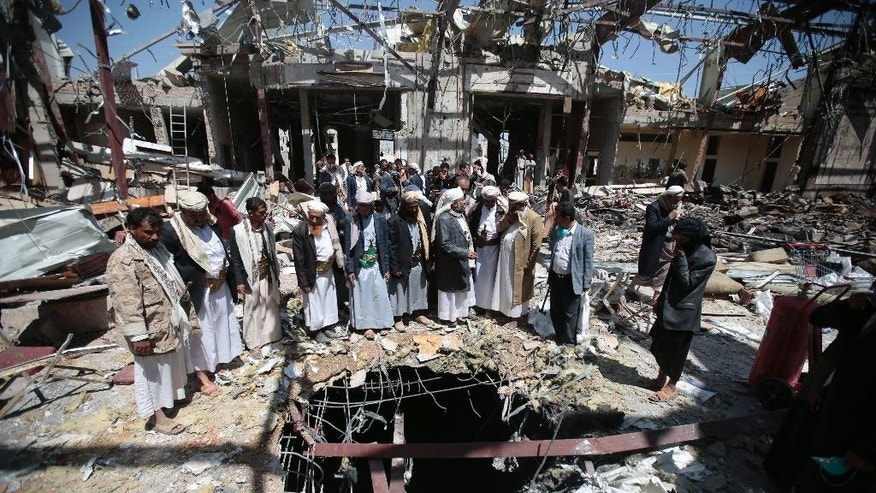 FILE- In this Thursday, Oct. 13, 2016 file photo, members of the Higher Council for Civilian Community Organization inspect a destroyed funeral hall as they protest against a deadly Saudi-led airstrike on a funeral hall six days ago, in Sanaa, Yemen. An investigation team with the Saudi-led coalition says wrong information is behind the lethal bombing of a packed funeral in the Yemeni capital Sanaa, which left around 140 dead and over 600 people injured. (AP Photo/Hani Mohammed, File)