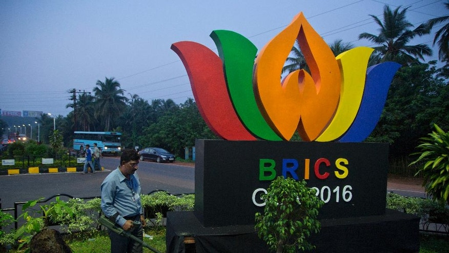 An Indian policeman from bomb squad checks a round about with a huge BRICS logo, in Goa, Friday, Oct. 14, 2016.  The leaders of five big developing nations that banded together in 2009 as the so-called BRICS nations, are set to attend their annual summit Oct. 15-16, 2016 in a beach resort town in the western Indian state of Goa. But with their own economies now flagging, some analysts are questioning whether the group, consisting of Brazil, Russia, India, China and South Africa, still has clout in representing nearly half the world's population and a quarter of its economy at $16.6 trillion. (AP Photo/Anupam Nath)