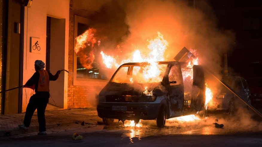 A car burns outside a nightclub near the University of the Witwatersrand in Johannesburg, South Africa, Friday, Oct. 14, 2016. Cars were set alight and businesses damaged as chaos erupted after a curfew was instituted at the university, where police released tear gas to prevent protesters on campus from setting gas canisters alight. (AP Photo/Yeshiel Panchia)
