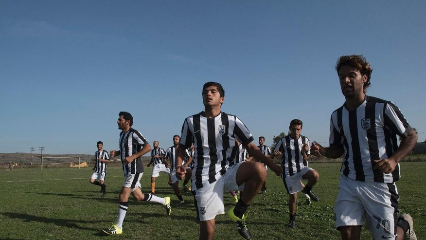 In this photo taken on Friday, Oct. 14, 2016, players of Herso camp warm up before the game between the refugee teams from Nea Kavala camp and from Herso camp, in the village of Nea Kavala, northern Greece. Soccer players and fans from Syria and Iraq got a break from life at migrant camps to play a match organized by a government migration agency, launching a tournament that will include local amateur Greek teams. The first game on Friday was slow paced, with white lines on the pitch only half painted in. Spectators were seated on grass or on the terrace of a half-built home to get a decent view. (AP Photos/Giannis Papanikos)