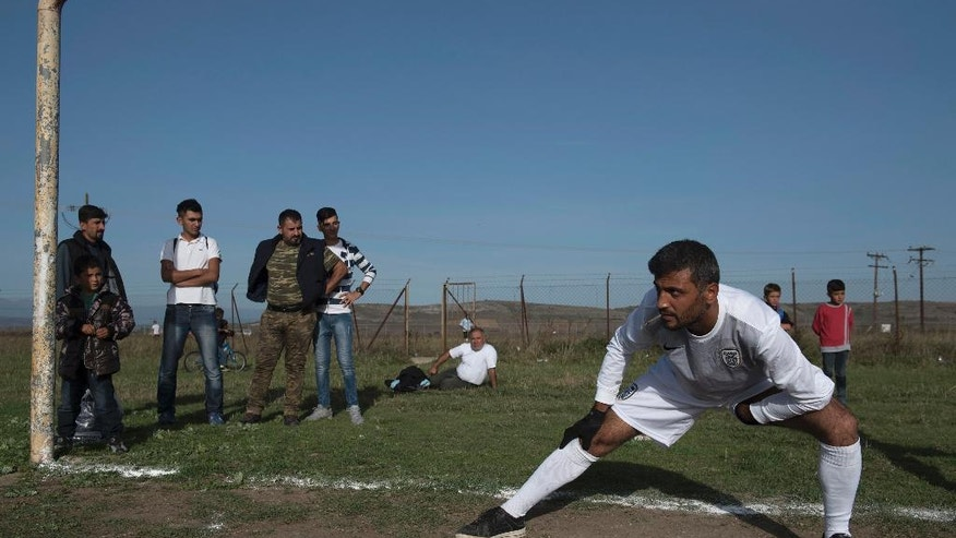 In this Friday, Oct. 14, 2016 photo, the goalkeeper of the Herso camp warms up before the game between refugee teams from Nea Kavala camp and from Herso camp, in the village of Nea Kavala, northern Greece.  Soccer players and fans from Syria and Iraq got a break from life at migrant camps to play a match organized by a government migration agency, launching a tournament that will include local amateur Greek teams. The first game on Friday was slow paced, with white lines on the pitch only half painted in. Spectators were seated on grass or on the terrace of a half-built home to get a decent view. (AP Photos/Giannis Papanikos)