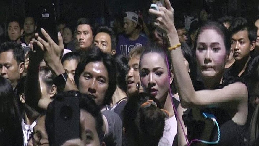 In this Friday, Oct. 14, 2016 image made from video, people gather outside a soy milk shop on the Thai resort island of Phuket. Police and soldiers on the Thai resort island of Phuket dispersed a mob of several hundred people seeking a confrontation with a man they believed insulted the country's king, who died this week. (AP Photo)