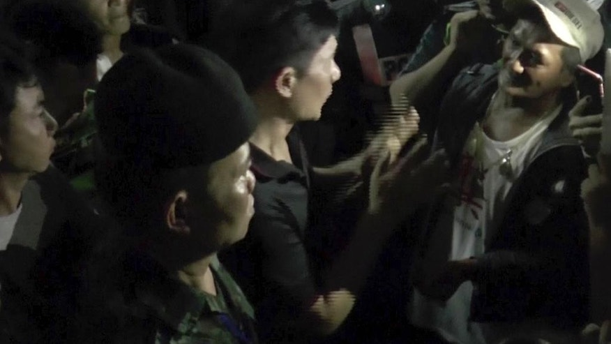 In this Friday, Oct. 14, 2016 image made from video, an official, center in black shirt, tires to calm down people who gather outside a soy milk shop on the Thai resort island of Phuket. Police and soldiers on the Thai resort island of Phuket dispersed a mob of several hundred people seeking a confrontation with a man they believed insulted the country's king, who died this week. (AP Photo)