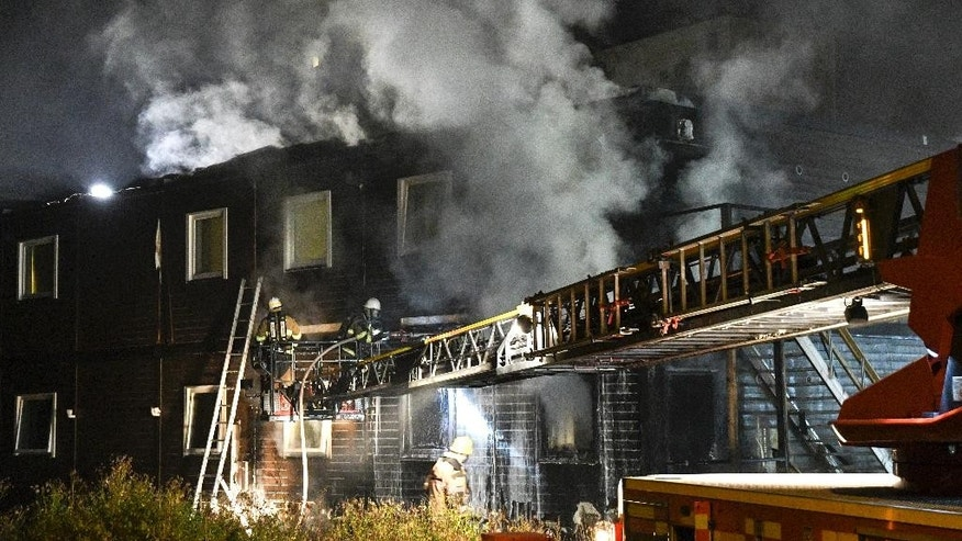 Firefighters extinguish a fire that broke out during the night Sunday Oct. 16, 2016, after evacuating residents from the refugee accommodation in Fagersjo, south of Stockholm, Sweden.  Investigators are treating the matter as possible arson. (Johan Nilsson / TT via AP)