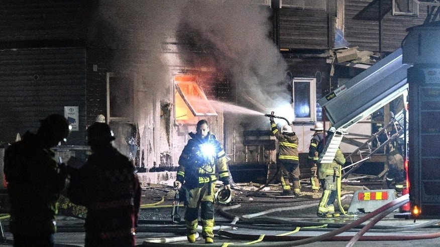Firefighters extinguish a fire that broke out during the night, early Sunday Oct. 16, 2016, after evacuating residents from the refugee accommodation in Fagersjo, south of Stockholm, Sweden.  Investigators are treating the matter as possible arson. (Johan Nilsson / TT via AP)