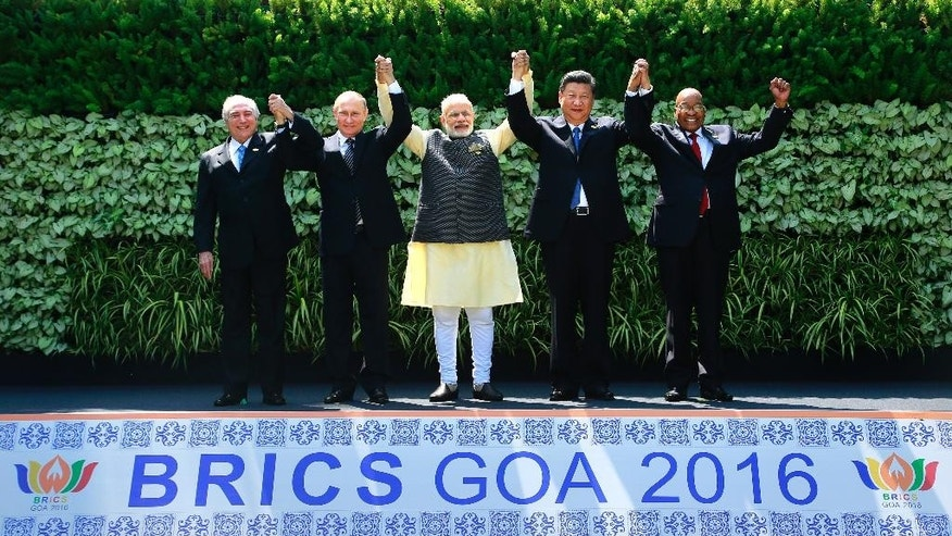 Leaders of BRICS countries, from left, Brazilian President Michel Temer, Russian President Vladimir Putin, Indian Prime Minister Narendra Modi, Chinese President Xi Jinping, and South African President Jacob Zuma raise their hand for a group photo at the start of their Summit in Goa, India, Sunday, Oct. 16, 2016. Leaders of five of the world's fast-rising powers are meeting in the southwestern Indian state of Goa for their annual summit at a time when their ability to shape the global dialogue on international politics and finance is increasingly being questioned. Brazil, Russia, India, China and South Africa, or BRICS, face the tough task of asserting their growing influence as a power group even as they bridge their own trade rivalries to help grow their economies. (AP Photo/Anupam Nath)