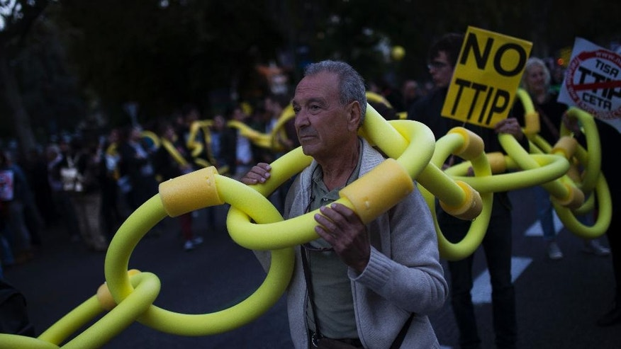 A man carries a long foam-rubber chain with others during a protest against the Trans-Atlantic Trade and Investment Partnership, or TTIP, in Madrid, Saturday, Oct. 15, 2016. Several hundred people have gathered in Madrid to protest against the Transatlantic Trade and Investment Partnership, a major free trade deal between the United States and the European Union. (AP Photo/Francisco Seco)