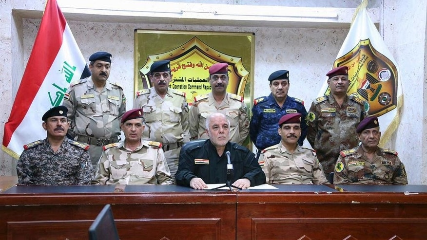 This photo released on his official Facebook page shows Iraqi Prime Minister Haider al-Abadi, center, surrounded by top military and police officers as he announces the start of the operation to liberate the northern city of Mosul from Islamic State militants early Monday, Oct. 17, 2016. The push to retake Mosul will be the biggest military operation in Iraq since American troops left in 2011 and, if successful, the strongest blow yet to the Islamic State. (Iraq Prime Minister's office via AP)