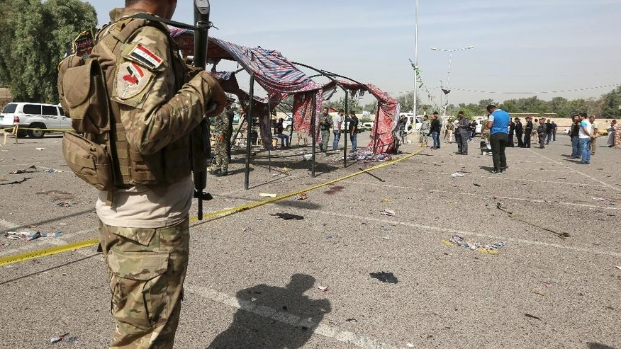 Iraqi security forces gather at the site of a bomb attack in Baghdad, Iraq, Sunday, Oct. 16, 2016. A police officer said Sunday's attack took place in Baghdad's Shiite-dominated Jadriyah neighborhood on the Tigris River, where the explosive-laden bomber approached Shiites commemorating the 7th century death of Imam Hussein, the grandson of the Prophet Muhammad. (AP/Photo/Hadi Mizban)