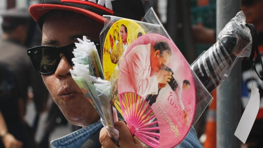 A Thai vendor sells commemorative fans as mourners gather to pay their respects to the late Thai King Bhumibol Adulyadej outside the Grand Palace in Bangkok, Thailand, Sunday, Oct. 16, 2016. Tens of thousands of people are thronging at the palace complex to pay their last respects to a beloved monarch who dominated the memories of generations of Thais. (AP Photo/Charles Dharapak)