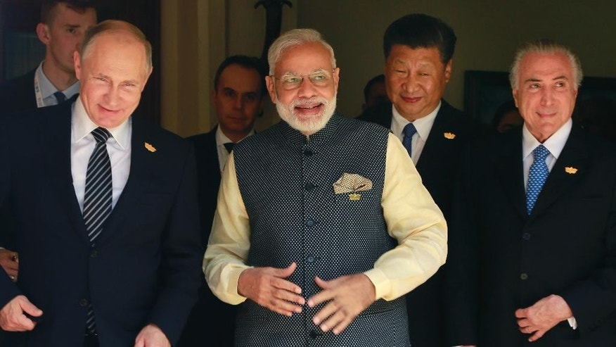 Leaders of BRICS countries, from left, Russian President Vladimir Putin, Indian Prime Minister Narendra Modi, Chinese President Xi Jinping, and Brazilian President Michel Temer, arrive for a group photo for media at the start of the summit in Goa, India, Sunday, Oct. 16, 2016. Leaders of five of the world's fast-rising powers are meeting in the southwestern Indian state of Goa for their annual summit at a time when their ability to shape the global dialogue on international politics and finance is increasingly being questioned. Brazil, Russia, India, China and South Africa, or BRICS, face the tough task of asserting their growing influence as a power group even as they bridge their own trade rivalries to help grow their economies. (AP Photo/Anupam Nath)