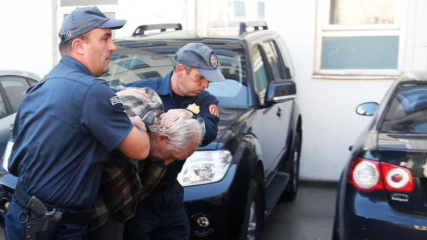 Montenegrin police officers escort a suspected man in Podgorica, Montenegro, Sunday, Oct. 16, 2016. Rising tensions amid a crucial election, Montenegrin police say they have arrested 20 people who are suspected of planning armed attacks after the vote that could determine whether the small Balkan state continues on its Western course or turns back to traditional ally Russia. (AP Photo/Darko Vojinovic)