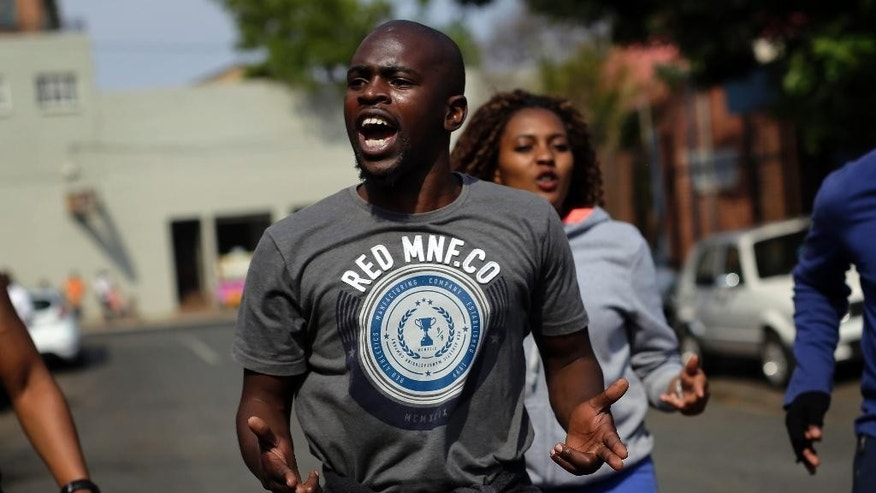"South African students dance outside Cleveland Police Station in Johannesburg, South Africa, Sunday Oct. 16, 2016, after a leader of university student protests for free education was arrested overnight. Mcebo Dlamini was detained during investigations into ""violence, criminality, intimidation,"" said South African Police. (AP Photo/Themba Hadebe)"