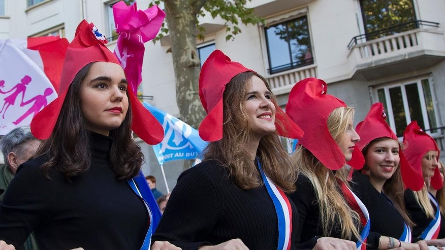 Demonstrators dressed as Marianne, the symbol of the French republic since the 1789 revolution march during a rally to protest gay marriage in Paris, Sunday, Oct. 16, 2016. Thousands of people have marched in Paris to call for the repeal of a law allowing gay marriage, six months before France's next presidential election. (AP Photo/Michel Euler)
