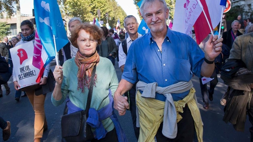 A woman march with her husband hand in hand during in a rally to protest gay marriage in Paris, Sunday, Oct. 16, 2016. Thousands of people have marched in Paris to call for the repeal of a law allowing gay marriage, six months before France's next presidential election. (AP Photo/Michel Euler)