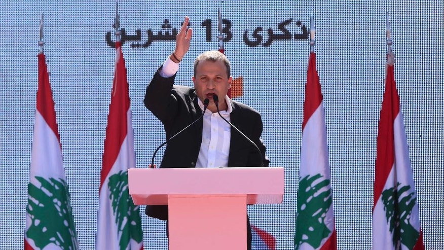 "Head of the Free Patriotic Movement and Lebanese Foreign Minister Gibran Bassil speaks during a rally near the presidential palace in the Beirut suburb of Baabda, Lebanon, Sunday, Oct. 16, 2016. Christian leader Michel Aoun said during a speech that respecting Lebanon's equal power sharing system between Christians and Muslims will pave the way for building a proper state. Arabic on the picture reads ""Memory of 13 October.""(AP Photo/Hassan Ammar)"